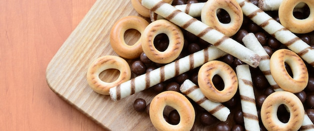 Crispy tubules, chocolate melting balls and bagels lie on a wooden surface. mix of various sweets