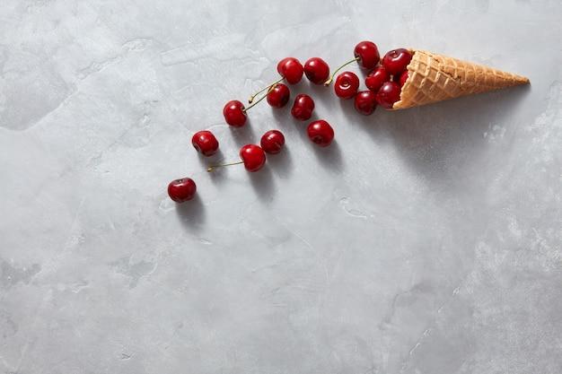 Хрустящая вафельная чашка с здоровой органической вишней ягод в сладкой чашке на сером каменном фоне, место под текстом. летняя концепция домашнего мороженого.
