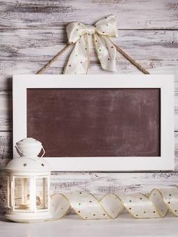 ぼろぼろの木製の壁と休日のリボンの上の挨拶のためのボードとクリスマスのランタン