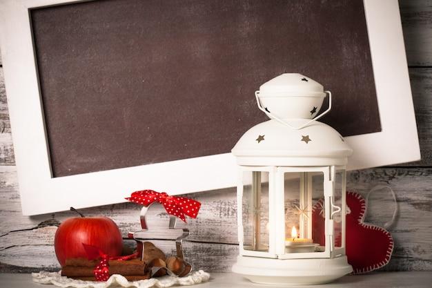 ぼろぼろの木製の壁の上の挨拶のためのボードとクリスマスのランタン
