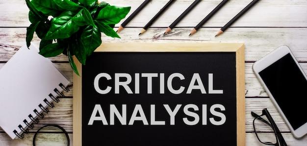 Критический анализ написано белым на черной доске рядом с телефоном, блокнотом, очками, карандашами и зеленым растением.