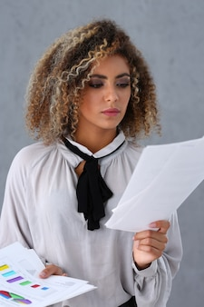 Critical lady examining business documents