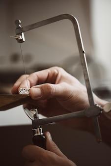 전문적으로 조정 가능한 은반지를 만드는 보석상 손의 중요한 순간 근접 촬영 사진