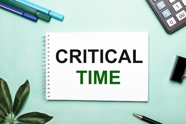 Критическое время написано на белом листе на синем фоне рядом с канцелярскими принадлежностями и листом шеффлера. призыв к действию. мотивационная концепция