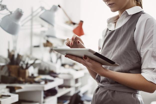 디지털 태블릿으로 온라인 작업을 하는 crm 시스템의 주요 여성 생산 관리자