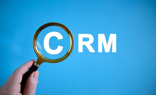 Crm - text with a magnifying glass on a blue background