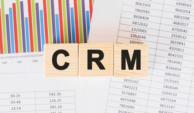 Crm word written on wood block. faqs text on table, concept.