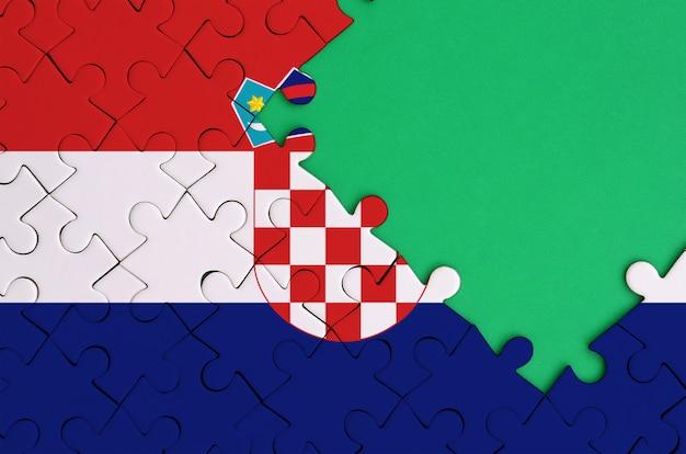크로아티아 국기는 오른쪽에 무료 녹색 복사 공간이있는 완성 된 직소 퍼즐로 그려져 있습니다.