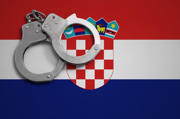 Croatia flag  and police handcuffs. the concept of crime and offenses in the country