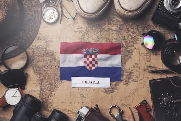 Croatia flag between traveler's accessories on old vintage map. overhead shot