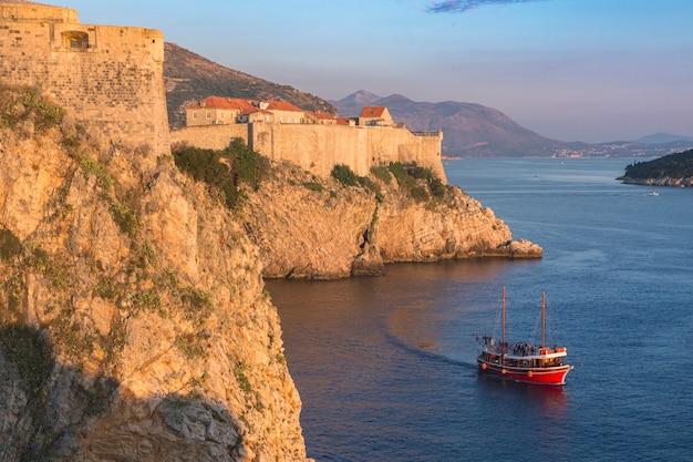 크로아티아. 남쪽 달마티아. 두브로브니크, 중세 성벽 도시 및 바다를 건너는 읽기 보트의 공중 전망