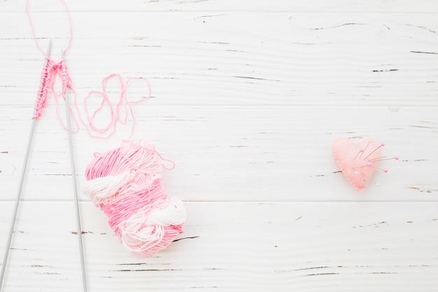 핑크 하트 모양 쿠션의 바느질 핀 근처의 크로 셰 뜨개질 및 원사