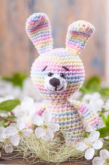 Crochet bunny on the background of delicate cherry flowers.