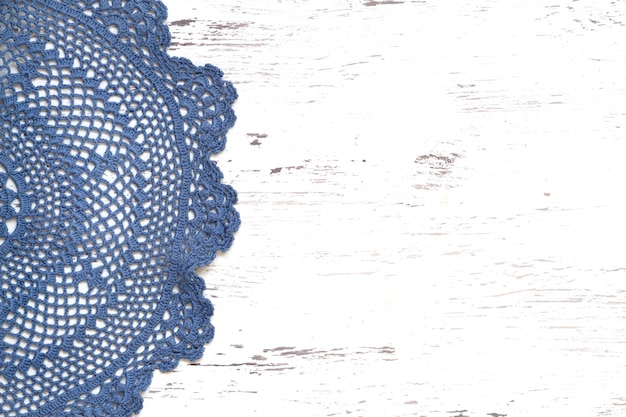 Crochet doily border over white wooden table top view with copy space