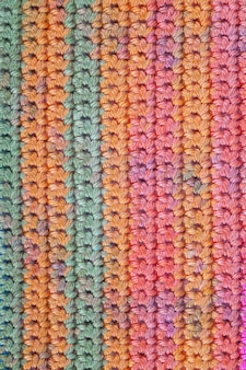 Crochet, handmade, needlework. close up macro background texture of striped knitted texture.