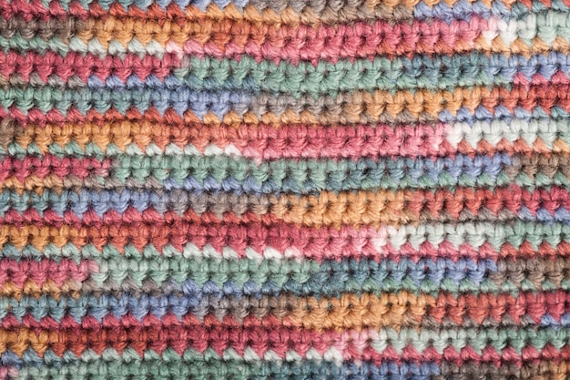 Crochet, handmade, needlework. multicolored skein of threads and a hook background