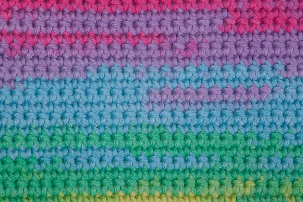 Crochet, handmade, needlework. multicolored skein of threads and a hook on an old wooden background.