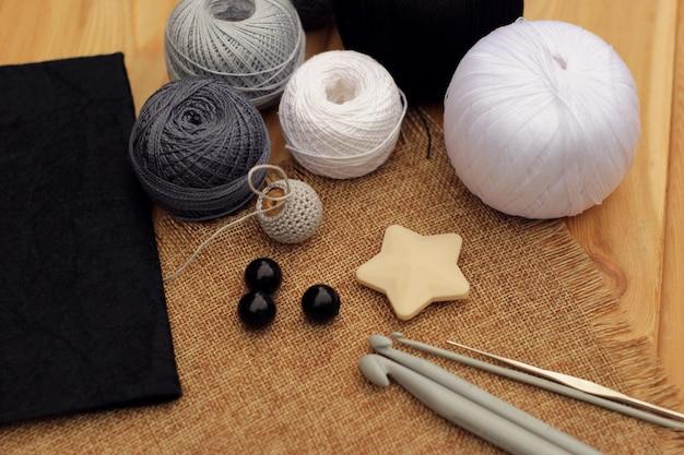 Вяжите крючки и шарики из хлопковой нити на деревянном столе, скопируйте пространство.