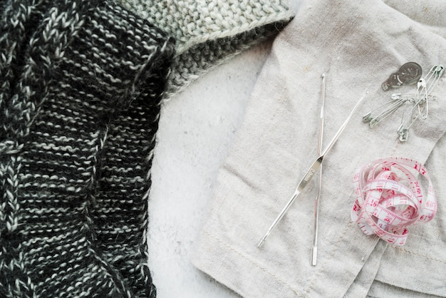 Crochet needles; knitwear fabric; measuring tape; safety pins on white textured backdrop