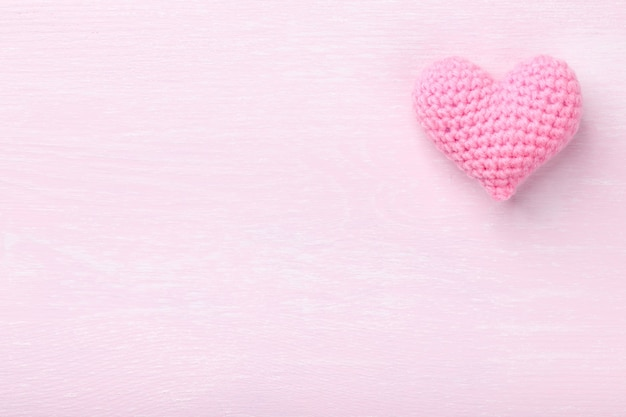 Crochet pink heart on pink wooden background