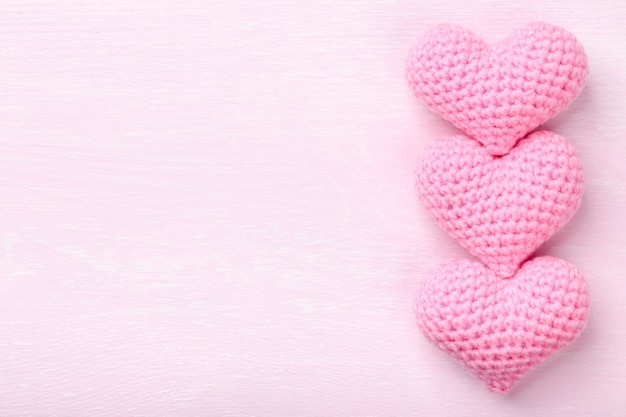 Crochet pink hearts on pink wooden background