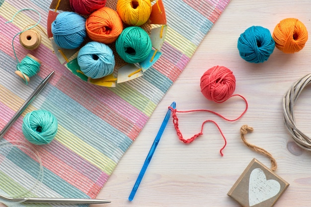 Crochet, top view on yarn balls on light wood