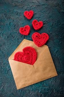 暗い表面にバレンタインのハートと封筒をかぎ針編み。
