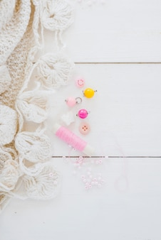 Crochet white fabric; beads and pink spool on wooden desk