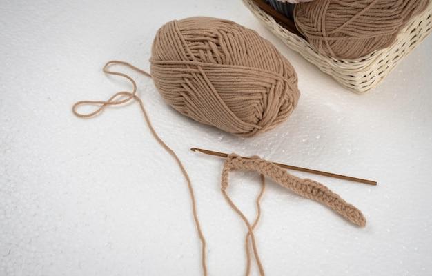 나무 코바늘과 갈색 실 볼로 크로 셰 뜨개질 작업,