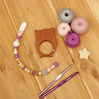 かぎ針編みの赤ちゃんのおしゃぶりホルダー。ヤーンボールとかぎ針編みのフック。フラットレイ