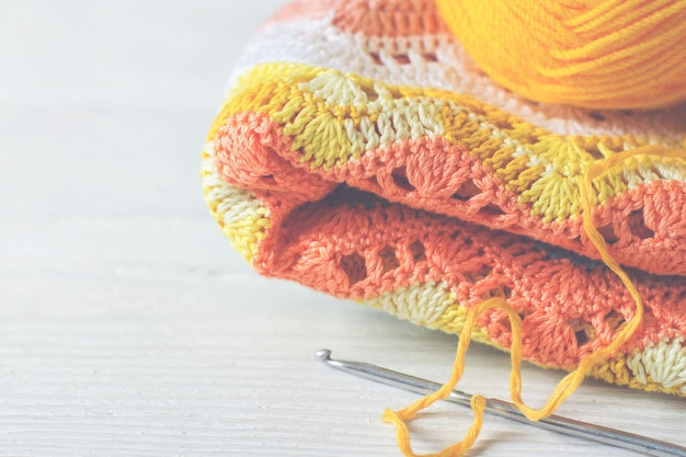 뜨개질을 한 수제 배경입니다. 옐로우 로즈 컬러의 니트 원단, 볼 실과 크로셰 후크. 빈티지 토닝, 복사 공간