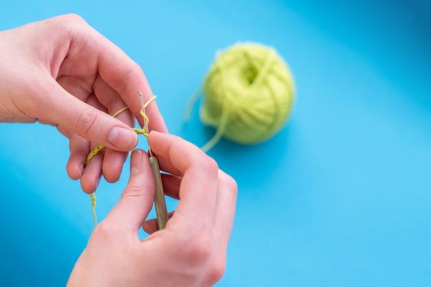 밝은 배경에 면과 크로셰 뜨개질을 한 손, 선택적인 초점, 복사 공간, 수제.