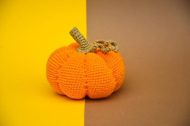 A crocheted orange pumpkin is isolated on a beigeyellow background autumn needlework