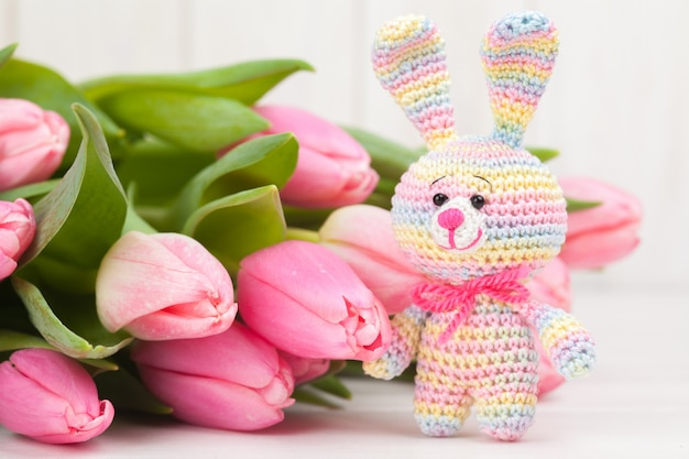Crocheted rabbit on the background of delicate pink tulips.