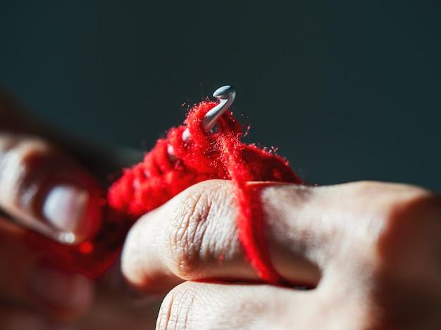 Вязание красной шерстяной пряжей крючком на темном фоне