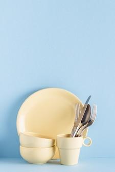 食器やカトラリー、青いパステル背景
