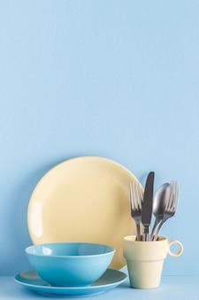 青いパステルカラーの背景に食器とカトラリー