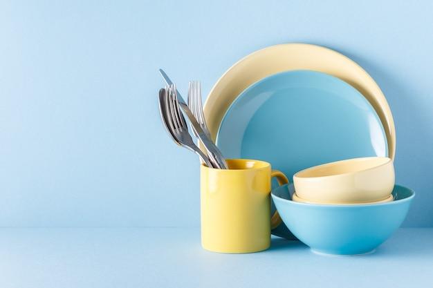 Посуда и столовые приборы на голубой пастели.