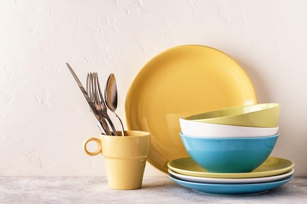 Посуда и столовые приборы на светлом столе с копией пространства.