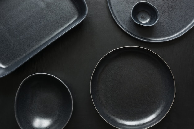 Crockery, clayware, black utensils and different stuff on black tabletop.