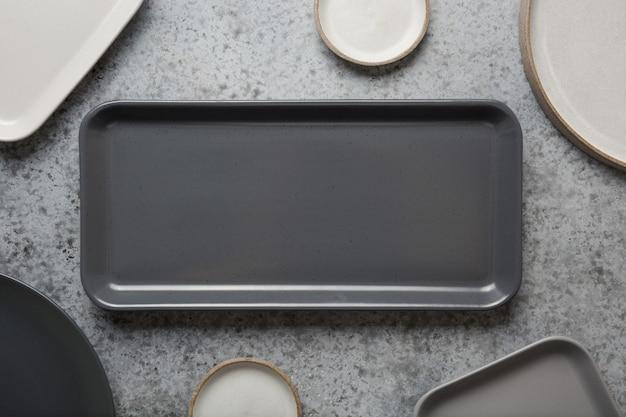 Посуда, глиняная посуда, пустая серая современная посуда и разные вещи на серой столешнице. вид сверху.