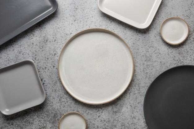 Посуда, глиняная посуда, пустая серая современная посуда и разные вещи на сером. вид сверху.