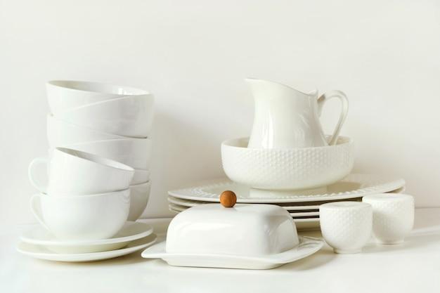 그릇, 접시,기구 및 흰색 테이블 위에 다른 흰색 물건.