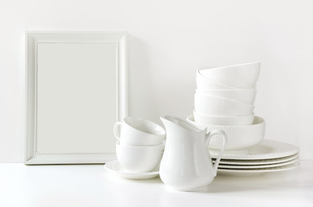 Crockery,dish, utensils and other different white stuff on white table-top.