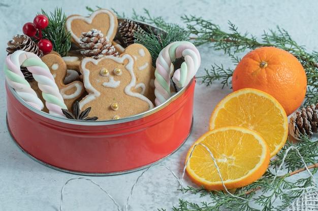Stoviglie piene di biscotti di natale fatti in casa e fette di arancia