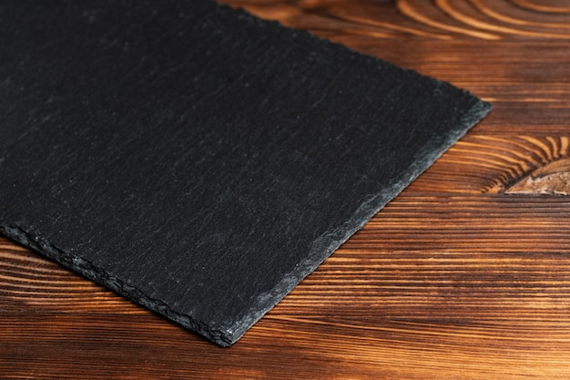 木製の背景に食器スレート、黒い石。