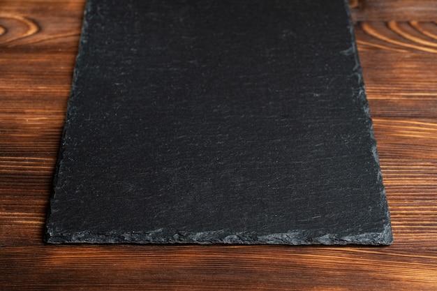 Посуда шифер, черный камень на деревянном фоне.