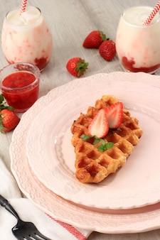 ピンクプレートのクロワッフルまたはクロワッサンワッフル。 croffleは韓国のバイラルケーキです。韓国産いちごミルク添え