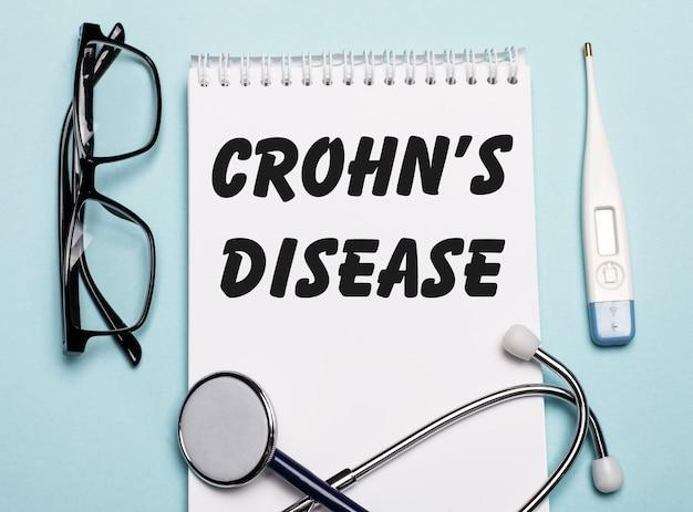 聴診器、ゴーグル、水色のテーブルの電子体温計の横にある白いメモ帳に書かれたクローン病。医療の概念。
