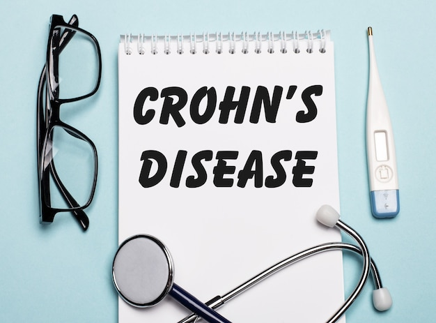 Crohns disease written on a white notepad next to a stethoscope, goggles, and an electronic thermometer on a light blue table. medical concept.